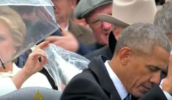 Obama and guests seek cover from rain